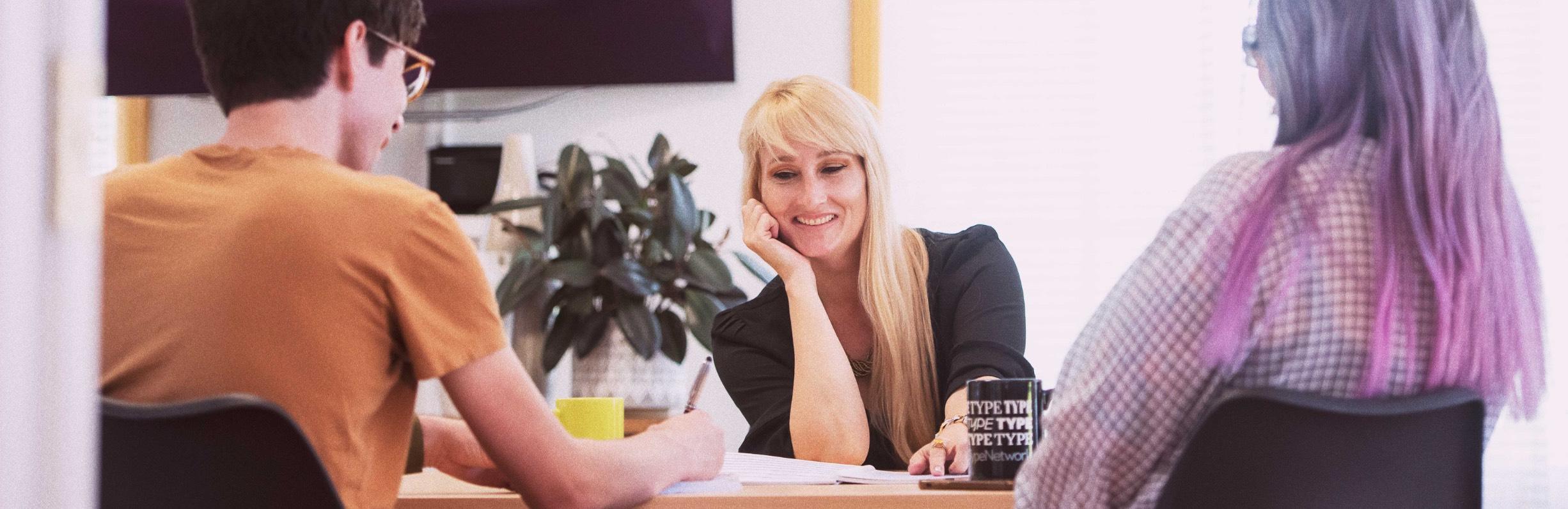 Three team members talking at a desk